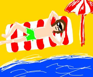 Laying on a beach under an umbrella