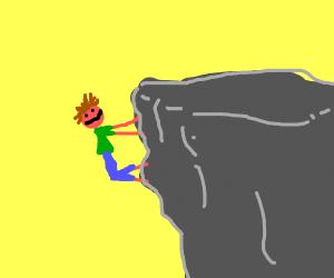 man climbs up a cliff