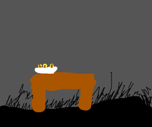 A taquito on a desk in a dark room
