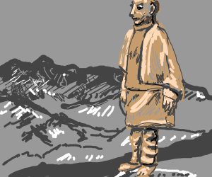 stone statue of a man behind mountain range