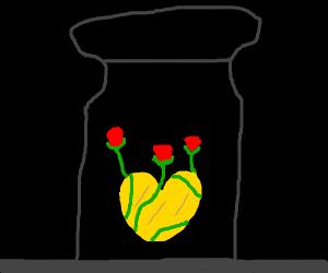 A golden heart w/ vines in a jar in the dark