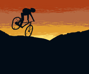 Mountain biker with backpack in sunset