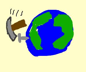 hammer smashin a nail in earth