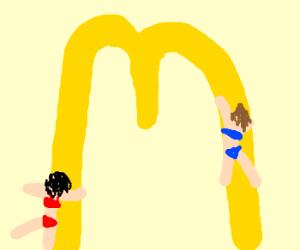 2 women in bikinis climb golden arches