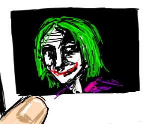 Polaroid of the Joker w/ a finger on it