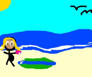 Pregnantchick cleaning surfboard onbeach