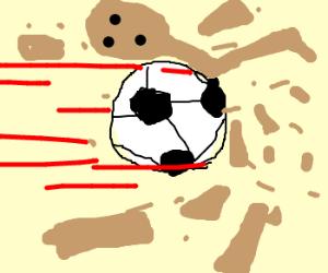 a soccer ball destroying a cardboard man