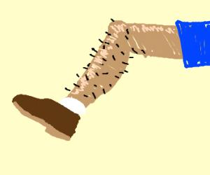 Brown shoe on hairy leg.