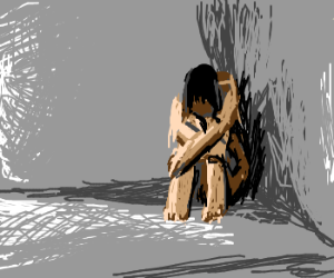 Man sitting in a corner of a grey room, crying