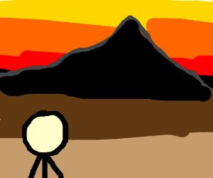 Man gazes at black mountainside
