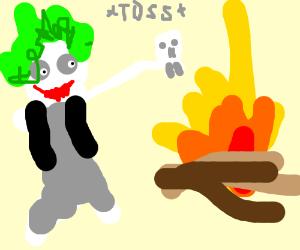 Joker tossing a skull into a campfire