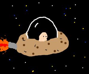 Potato astronaut flies cookie spaceship.