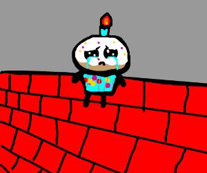 sad cupcake on brick wall
