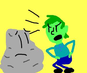 Green man squatting and screaming at rock.