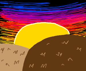 A sunset over a barren hill