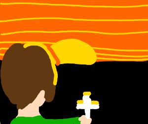 Boy contemplates horizon with crucifix