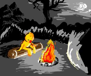 Yellmo sitting at a Camp Fire at Night