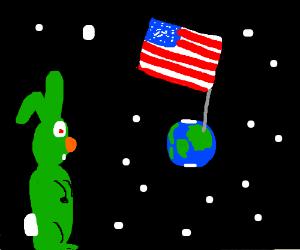 GreenBunnyStaresAtTheEarthWhichHasAGiantUSflag