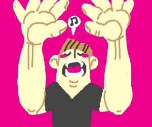 Blushing man with large hands singing.