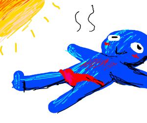 Blue man sun bathing in a red speedo