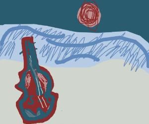 Big violin standing next to ocean at sunset